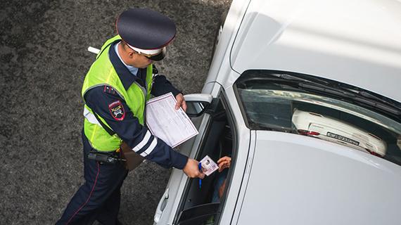 Инспектор ГИБДД проверяет наличие полиса ОСАГО